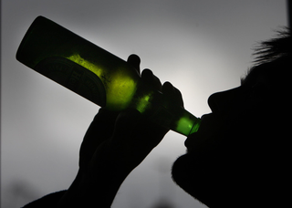 Silhouette of unidentified male teen drinking beer
